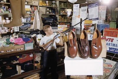 Boy Holding Shotgun in Sporting Goods Store by William P. Gottlieb