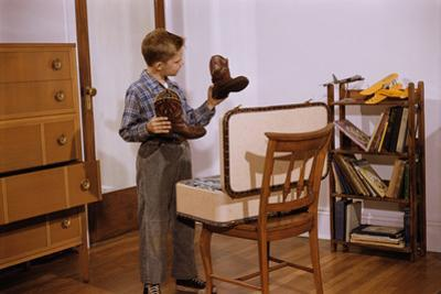 Boy Looking at Cowboy Boots by William P. Gottlieb