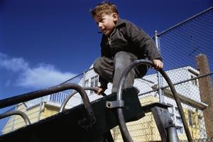 Boy Playing on Playground Slide by William P. Gottlieb