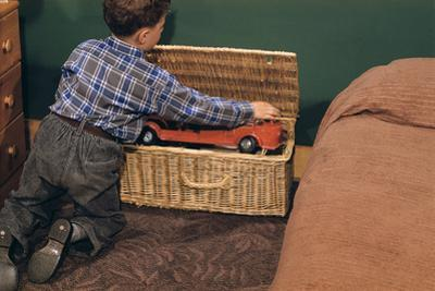 Boy Removing Fire Engine from Toy Chest by William P. Gottlieb