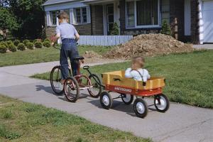 Boy Riding Tricycle and Towing Wagon by William P. Gottlieb