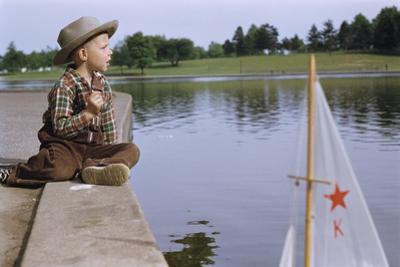 Boy Sitting by Lake in Cowboy Hat by William P. Gottlieb