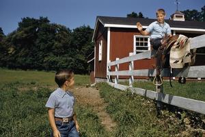 Boy Sitting on Fence Waving to Friend by William P. Gottlieb
