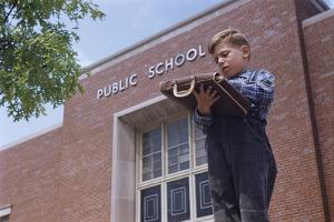 Boy Standing Outside School by William P. Gottlieb