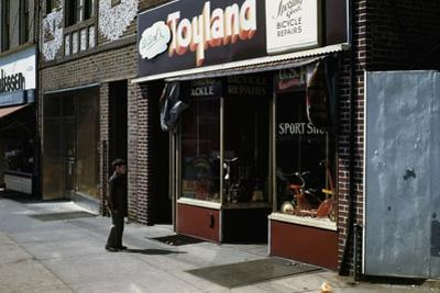 Boy Standing Outside Toyland by William P. Gottlieb