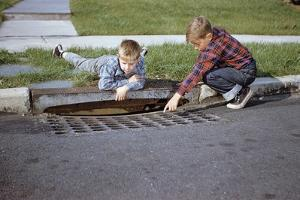 Boys Looking into Grate by William P. Gottlieb