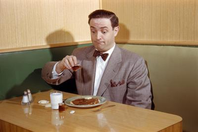 Businessman Pouring Syrup on Pancakes by William P. Gottlieb