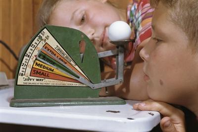 Children Measuring Egg on Scale by William P. Gottlieb