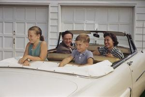 Family Sitting in Car Outside Garage by William P. Gottlieb