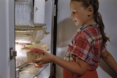 Girl Removing Raspberries from Freezer by William P. Gottlieb