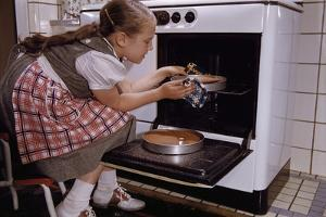 Girl Wearing Apron Removing Cakes from Oven by William P. Gottlieb