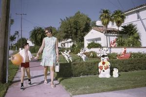 Mother and Son Walking by Christmas Decorations on Yards by William P. Gottlieb