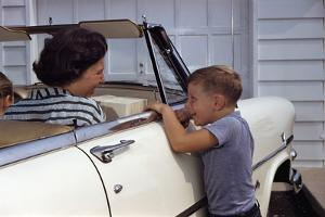 Mother Sitting in Car Laughing with Son by William P. Gottlieb
