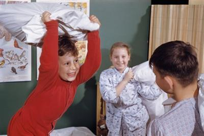 Siblings Having Pillow Fight by William P. Gottlieb