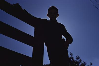 Silhouette of Boy Leaning Against Fence by William P. Gottlieb