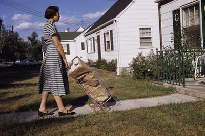 Woman Pushing Shopping Cart to House by William P. Gottlieb