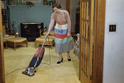 Woman Vacuuming Living Room by William P. Gottlieb