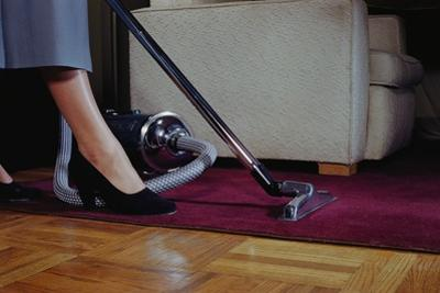 Woman Vacuuming Rug by William P. Gottlieb