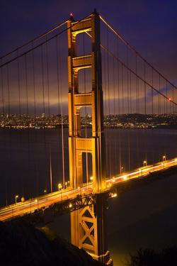 Golden Gate Bridge, Night Vertical with Lights of San Francisco, California in Background by William Perry
