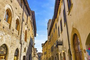 Hotel and bars on Medieval street, San Gimignano, Tuscany, Italy. by William Perry