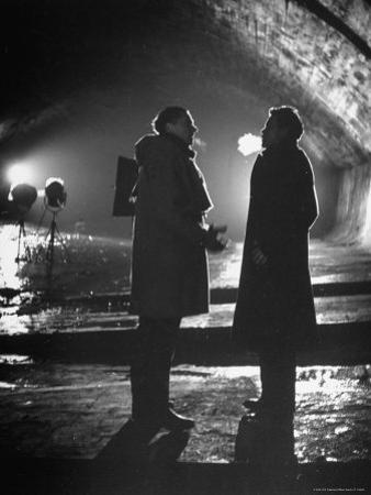 "Carol Reed Coaching Orson Welles as They Stand Against Floodlights During Filming ""The Third Man."""