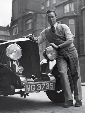 Richard Todd Leaning on Front of Car by William Sumits