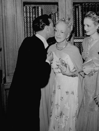 Famed Interior Decorator Lady Mendl Being Kissed by Oliver Messel at the British Embassy by William Vandivert