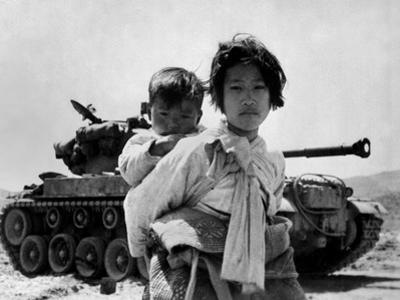With Her Brother on Her Back, a War Weary Korean Girl Tiredly Trudges by a Stalled M-26 Tank
