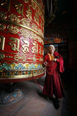 https://imgc.allpostersimages.com/img/posters/woman-and-prayer-wheel-bodhnath-stupa-kathmandu-nepal_u-L-Q1GYL220.jpg?artPerspective=n