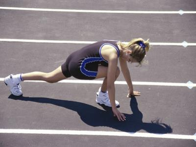 Woman at the Starting Pose on a Running Track