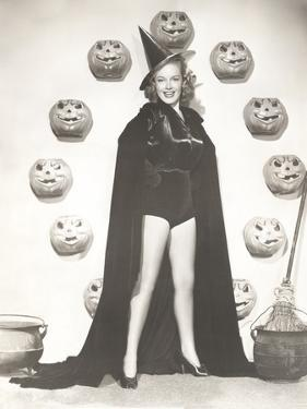 Woman in Witch Costume Surrounded by Carved Pumpkins