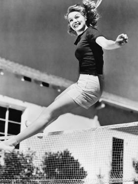 Woman Leaping over a Tennis Net