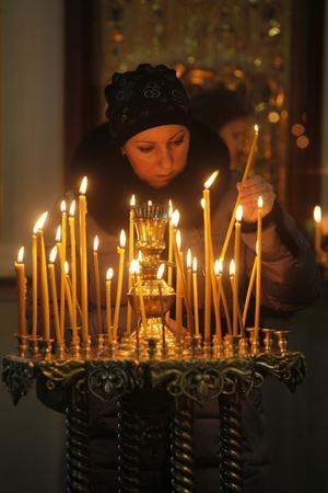 https://imgc.allpostersimages.com/img/posters/woman-lighting-a-candle-trinity-cathedral_u-L-Q1GYLX20.jpg?artPerspective=n