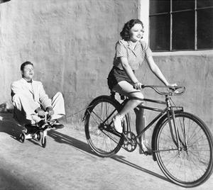 Woman on Bicycle Man Tricycle
