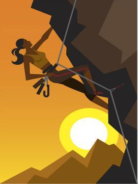 Woman Rock Climber Scaling Cliff at Dawn