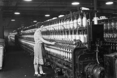 Woman Standing at Long Row of Bobbins, at a Textile Factory
