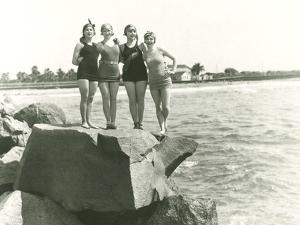 Women in Bathing Suits Posing on Rock