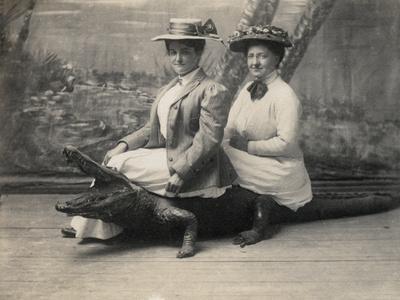 https://imgc.allpostersimages.com/img/posters/women-sitting-on-a-stuffed-alligator-c-1905_u-L-PPQX3O0.jpg?artPerspective=n