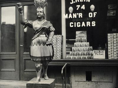 https://imgc.allpostersimages.com/img/posters/wooden-statue-in-front-of-cigar-shop_u-L-PZOKNB0.jpg?artPerspective=n
