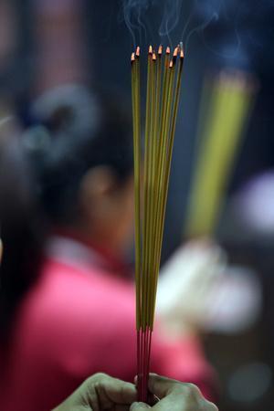 https://imgc.allpostersimages.com/img/posters/worshipper-burning-incense-sticks-taoist-temple-jade-emperore-pagoda-chua-phuoc-hai_u-L-Q1GYJ0N0.jpg?artPerspective=n
