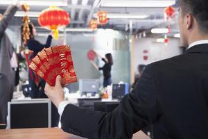 Businessman Holding Red Envelopes and Coworkers Hanging Decorations for Chinese New Year by XiXinXing