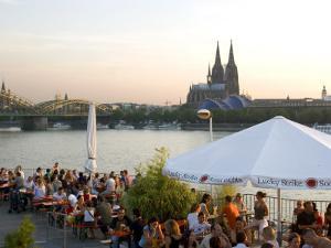 People at Trendy Rheinterrassen Bar and Restaurant Beside the River Rhine, Cologne, Germany by Yadid Levy