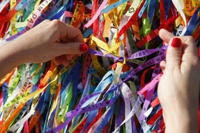 Woman Tying Lucky Ribbon at Igreja Nosso Senhor do Bonfim Church, Salvador, Bahia, Brazil by Yadid Levy