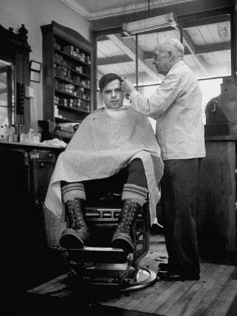 Elderly Barber Cutting Young Man's Hair by Yale Joel