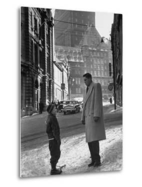 Ice Hockey Player Jean Beliveau, Standing in a Snow Covered Street Speaking to a Child by Yale Joel