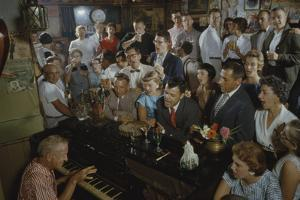 Low-Angle View of a Group of People as They Sing Along with a Pianist in a Unidentified Bar, 1959 by Yale Joel