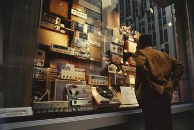 Man Looks at a Window Display of an Electronics Store, New York, New York, 1963 by Yale Joel