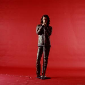 Rock Star Jim Morrison of the Doors Holding Microphone Alone as He Stands Against a Red Backdrop by Yale Joel