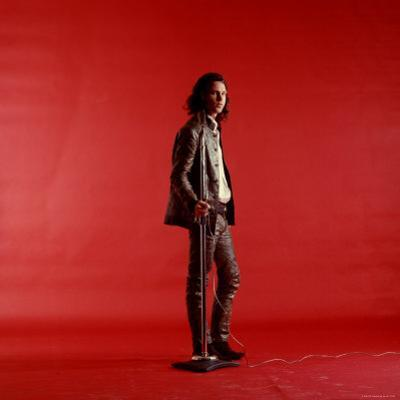 Rock Star Jim Morrison of the Doors Standing Alone Next to Microphone in Front of a Red Backdrop by Yale Joel