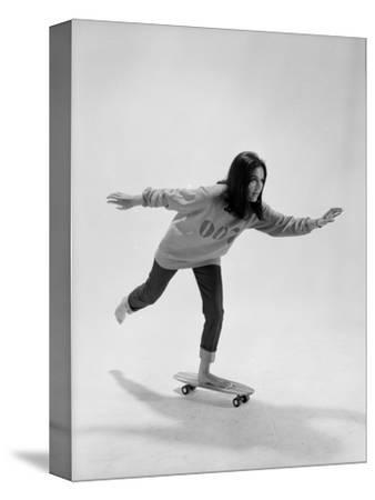 Studio Photos of Gloria Steinem Riding a Skateboard with a 007 James Bond Sweatshirt, 1965 by Yale Joel